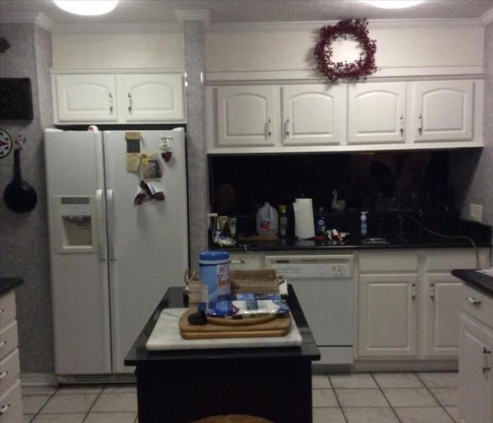 Kitchen with a Island Refrigerator and Cabinets with Storm Damage